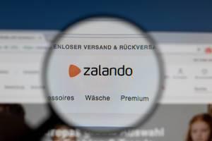 Zalando-Logo am PC-Monitor, durch eine Lupe fotografiert