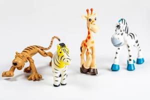 Zebra, giraffe and tiger toys on a white background