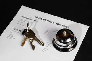 Zimmerreservation in Hotel mit Reservationsbestätigung, Hotelklingel und Schlüssel