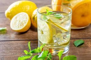 Zitronen-Cocktail mit Limonade, Zitrone, Minze und Eis auf Holztisch