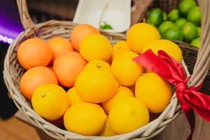 Zitronen und Orangen in einem Holzkorb - im Hintergrund Limetten