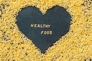 Zu Buchstaben geformte Pasta bildet Herz mit Schriftzug Healthy Food aus Nudeln