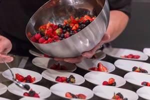 Zubereitung vieler Portionen eines Obstsalates mit unterschiedlichen Beeren