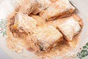 Zubereitung von gebratenem Hecht – in Mehl liegende Fischstücke auf Teller