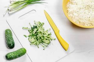 Zubereitung von Salat mit Gurken, Frühlingszwiebel und Sauerkraut, Aufnahme von oben
