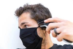 Zuhause wie beim Friseursalon mit dem Philips QC5115/15 Haarschneider. Mann schneidet sich die Haare selber mit Mundschutz. Porträt vor weißem Hintergrund