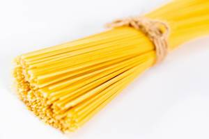 Zusammengebundene, goldgelbe Spaghetti vor weißem Hintergrund
