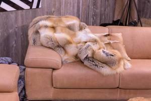 Zusammengeknüllte Decke und Zierkissen aus Pelz liegen auf braunem Ledersofa