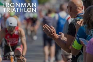 """Zuschauer feuern Radrennfahrer beim sportlichen Event an, neben dem Bildtitel """"Ironman Triathlon"""""""