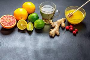 Zutaten für die Herstellung von immunitätssteigernden natürlichen Getränk mit Zitronen, Orangen, Ingwer, Honig, Grapefruit, Limette und Hagebutten