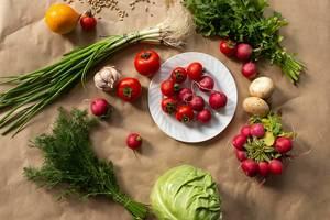 Zutaten für ein gesundes, veganes Essen, mit Knoblauchknolle, Radieschenstrauch, Kopfsalat und frischem Dill