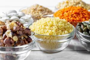 Zutaten für eine gesunde Diät und Ernährung, in Glasschalen, auf weißem Holztisch