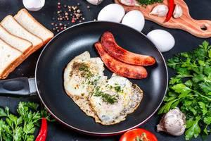 Zutaten für Frühstück und Spiegeleier in einer Pfanne