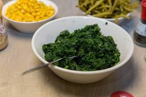 Zutaten für Raclette wie Spinat, Maissalat, ganze Bohnen, Pfeffermühle und Soße auf Holztisch