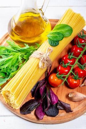 Zutaten, um Spaghetti zu kochen, auf einem runden Küchenbrettchen aus Holz mit Olivenöl in einer Glaskaraffe