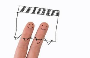 Zwei angemalte Finger mit lächelndem Gesicht, halten fröhlich eine Filmklappe in den Händen