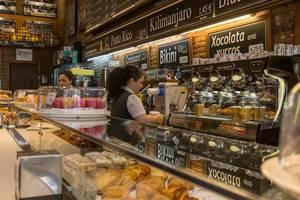 Zwei Angestellte in Arbeitskleidung, hinter der Ladentheke einer spanischen Bäckerei in Barcelona mit allerlei Gebäck und Kaffee