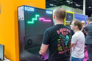 Zwei Besucher spielen auf einem Arcade-Automaten