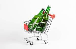 Zwei Bierflaschen stehen in Einkaufswagen vor weißem Hintergrund