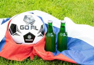 Zwei Bierflaschen und ein Fußball auf russischer Fahne