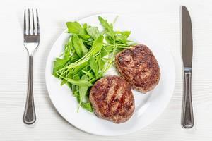 Zwei Buletten neben Rucola auf einem weißen Teller mit Messer und Gabel