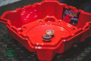 Zwei bunte Beyblade Zirkel in dafür hergestellter, roter Beyblade Burst Arena