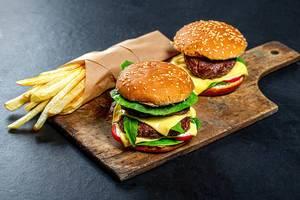 Zwei Burger und Pommes in Papier gewickelt, auf einem rustikalen Holzbrett