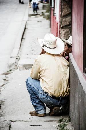 Zwei Cowboys mit weißen Cowboyhüten sitzen auf der Straße und unterhalten sich