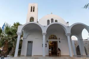 Zwei Damen sitzen auf Stühlen vor dem Eingang der heiligen Pfarrkirche Pantanassis in Naoussa auf Paros