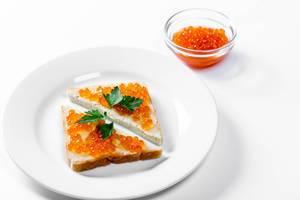 Zwei dreieckige Sandwiche mit gesalzenem rotem Kaviar auf weißem Hintergrund