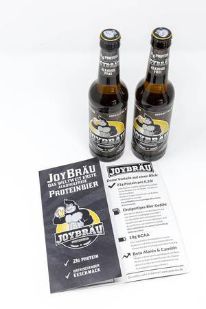 Zwei Flaschen stehend mit Broschüre - Joy Bräu weltweit erstes Alkoholfreies Proteinbier mit hohem Eiweißanteil, BCAA und Carnitin auf weißem Hintergrund