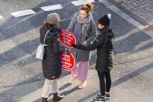 Zwei Frauen bekommen ein Demonstrationsschild mit der Aufschrift: Stop Klimakrise, Stop GroKo