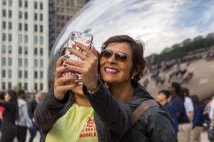 Zwei Frauen lächeln und machen ein Selfie vor dem Cloud Gate vom Künstler Anish Kapoor in Chicago