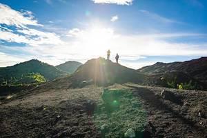 Zwei Freunde stehen auf dem Pacaya Vulkan in Guatemala und genießen die Sonne