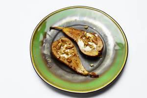 Zwei gebackene halbe Birnen mit gehackten Nüssen auf grünem Teller