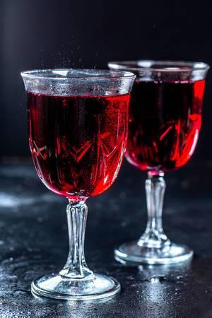 Zwei gefüllte Kristallgläser mit Rotwein vor dunklem Hintergrund