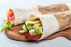 Zwei gerollte Shawarma mit buntem Gemüse auf hölzernem Küchenbrett vor weißem Hintergrund