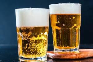zwei Gläser helles Bier mit Schaumkrone vor dunklem Hintergrund
