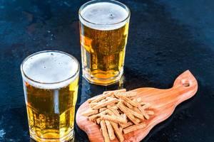 Zwei Gläser mit Bier und Aperitif-Gebäck auf Holzbrett auf dunklem Tresen