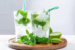 Zwei Gläser mit kaltem Mojito-Cocktail, frischen Minzblättern und Strohhalme