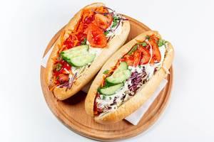Zwei Hot Dogs mit Kohl, Gurken, Tomaten, Karotten und Sauce auf einem Holzbrett auf weißem Hintergrund
