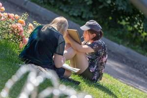 Zwei junge Frauen sitzen auf dem Rasen und malen im Gorki-Park