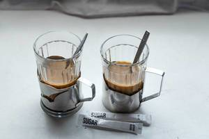 Zwei Kaffeegläser mit Zuckertüten auf weißem Tisch