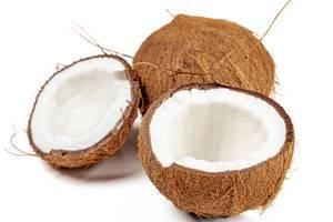 Zwei Kokosnusshälften ohne Kokosmilch und eine ganze Kokosnuss auf weißem Hintergrund Nahaufnahme