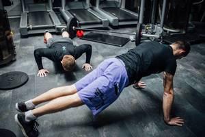 Zwei Männer machen Liegestütze am Boden eines Fitnessstudios