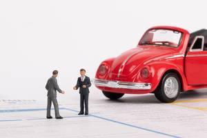 Zwei Männer und ein Oldtimer-Spielzeugauto auf einem Verkehrsunfallbericht