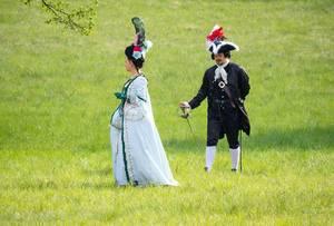 Zwei Menschen in barocken Kleidern in einem Schlosspark