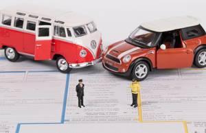 Zwei Oldtimer Spielzeugautos auf einem noch nicht ausgefüllten Schadensbericht