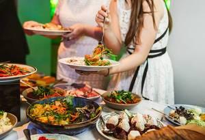 Zwei Personen stehen mit Tellern vor einem Buffet mit verschiedenen Gerichten