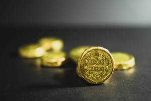 Zwei Pesos Schokomünze mit goldener Verpackung, steht aufrecht vor unscharfem Hintergrund